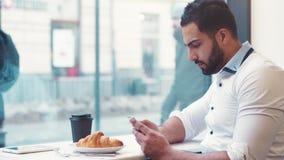 Idrotts- skäggig grabb som använder hans telefon vid fönstret av caféen stock video