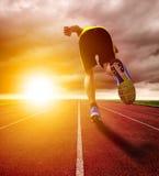 Idrotts- spring för ung man på loppspår med solnedgångbakgrund Royaltyfri Foto