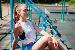 Idrotts- ung härlig blond kvinna efter sportar som utbildar att vila på sportjordning royaltyfria bilder