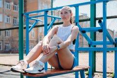 Idrotts- ung härlig blond kvinna efter sportar som utbildar att vila på sportjordning arkivfoto