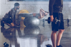 Idrotts- ung idrottskvinna som gör abs på konditionboll på idrottshallen Royaltyfria Bilder