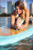 Idrotts- ung kvinna i elasticitet för framdel för SUPyogaövning i alun M Arkivfoton
