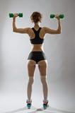 Idrotts- ung kvinna med hantlar i handen, bakre sikt Fotografering för Bildbyråer
