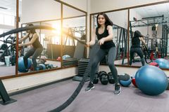 Idrotts- ung kvinna som övar i idrottshallen genom att använda stridrep Kondition sport, utbildning, folk, sunt livsstilbegrepp arkivfoto