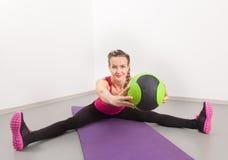 Idrotts- ung kvinna som gör övningar i idrottshallen Arkivbild