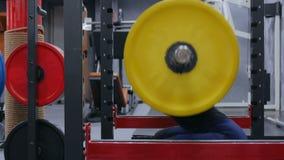 Idrotts- ung kvinna som gör övningar med skivstången på idrottshallen arkivfilmer