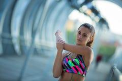 Idrotts- ung kvinna som sträcker för övning, medan lyssna till musik Arkivfoto