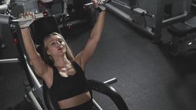 Idrotts- ung kvinna som utarbetar på konditionövningsutrustning på idrottshallen arkivfilmer