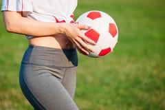 Idrotts- ung sexig flicka för närbild på fotbollfält med bollen på en solig sommardag med hans baksida till kameran arkivfoton