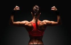 Idrotts- visningmuskler för ung kvinna av baksidan royaltyfri foto