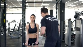 Idrottshallinstruktör som motiverar den trötta sportkvinnan för att göra övningen, sportlivsstil, handbok royaltyfri bild