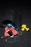 Idrottshalltillbehör för sportutbildning Dum-klockor, flaska och sportskor med en telefon på en golvbakgrund kopiera avstånd Arkivbilder