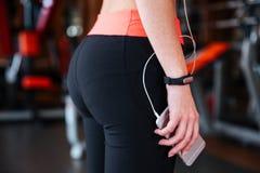 Idrottskvinna med den hållande mobiltelefonen för konditionbogserare i idrottshall royaltyfria bilder