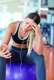 Idrottskvinna som använder en mobiltelefon i idrottshallen Royaltyfri Foto