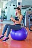 Idrottskvinna som använder en mobiltelefon i idrottshallen Royaltyfri Bild