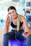 Idrottskvinna som använder en mobiltelefon i idrottshallen Arkivfoto