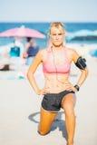 Idrottskvinna som gör utfall på stranden Fotografering för Bildbyråer