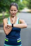 Idrottskvinna som kontrollerar hennes klocka för hjärtahastighet Arkivbilder