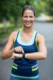 Idrottskvinna som kontrollerar hennes klocka för hjärtahastighet Fotografering för Bildbyråer