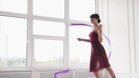 Idrottskvinnan dansar med ett band som kvinnan är förlovad i rytmisk gymnastik stock video
