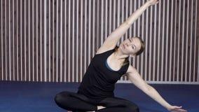 Idrottskvinnan gör yogaövningar i modern idrottshall arkivfilmer