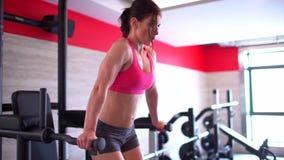 Idrottskvinnan i idrottshallen som gör sitta-UPS, press övar Muskulös kvinnlig idrottsman nen som gör absgenomkörare Begreppet av arkivfilmer