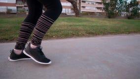 Idrottskvinnan joggar bara i stad parkerar i aftonen, närbild av hennes ben stock video