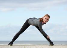 Idrottskvinnan som sträcker benet, tränga sig in utomhus Royaltyfria Bilder
