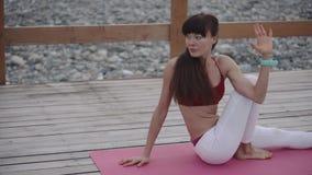 Idrottskvinnan sträcker muskler och senor av baksida och ben på yogautbildning lager videofilmer