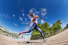 Idrottskvinnaspring och sprinta på löparbanan royaltyfri bild