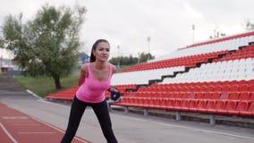 Idrottskvinnauppvärmning på sportstadion för rinnande konkurrens Brunettflickan gör lutar framåtriktat Flicka i rosa färg stock video