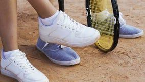 Idrottsmän som tätt sitter på den nervösa bänken, väntande på tennismatch, ben upp lager videofilmer