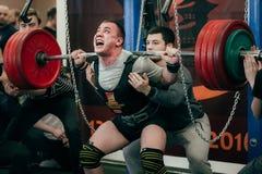Idrottsman nen av powerlifter squats skivstången Arkivfoto