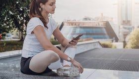 Idrottsman nen för den unga kvinnan i sportswearsammanträde parkerar, kopplar av in efter sportar som utbildar, använder smartpho Royaltyfri Fotografi