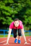 Idrottsman nen för ung kvinna i startande position Arkivbilder