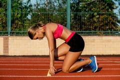 Idrottsman nen för ung kvinna på den startande positionen som är klar att starta ett lopp på löparbana Royaltyfri Foto