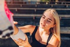 Idrottsman nen för ung kvinna som kontrollerar hennes ankel, når att ha kört på sportsground i sommar Skada under utbildning arkivfoton
