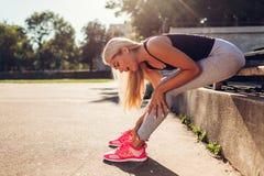 Idrottsman nen för ung kvinna som trycker på hennes ankel, når att ha kört på sportsground i sommar Skada under utbildning royaltyfri bild