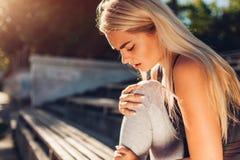 Idrottsman nen för ung kvinna som trycker på hennes knä, når att ha kört på sportsground i sommar Skada under utbildning arkivfoton