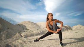 Idrottsman nen gör sträckning av musklerna av benen i naturen nära sanderna arkivfilmer