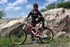 Idrottsman nen i en hjälm som rider en mountainbike på det tillbaka hjulet Arkivbild