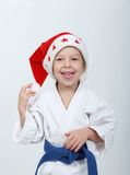 Idrottsman nen i kimono- och beanieSanta Claus le Arkivfoton