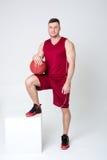 Idrottsman nen i sportar likformig och basket Arkivbild