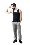 Idrottsman nen i svart ärmlös tröja som böjer armbiceps som ser muskler arkivbilder