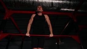 Idrottsman nen i svart kläder i idrottshallen utför ett maktuttag på horisontalstången En bred vinkelsikt underifrån arkivfilmer