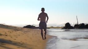Idrottsman nen kör längs stranden mot vita skumma havvågor arkivfilmer