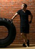 Idrottsman nen lutar mot det stora gummihjulet som grubblar utbildningsplanet mot bakgrunden av tegelstenväggen Fotografering för Bildbyråer