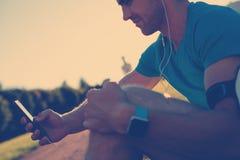 Idrottsman nen med le och lyssnande musik för smartphone i parkera arkivfoton