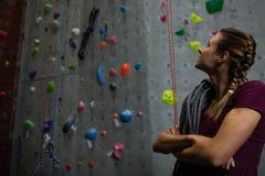 Idrottsman nen med repet som ser upp, medan stå, genom att klättra väggen i idrottshall Royaltyfri Fotografi