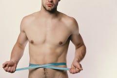 Idrottsman nen med starka muskler mäter midjan eller sixpacks Mätnings- och sportlivsstilbegrepp Man med blått Royaltyfri Bild